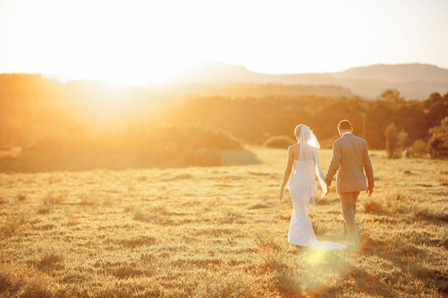wedding-couple-walking-infield-at-sunset