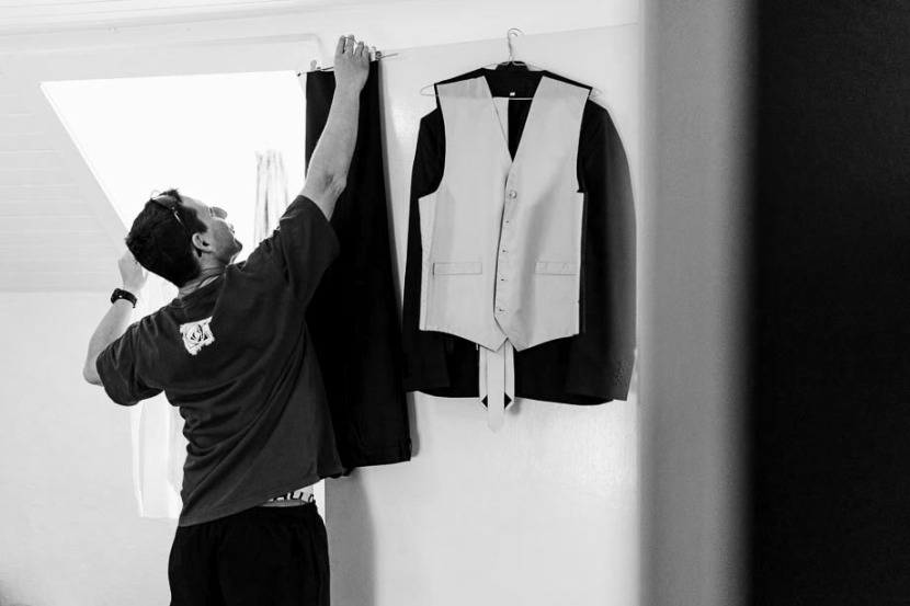 groom-hanging-wedding-suit