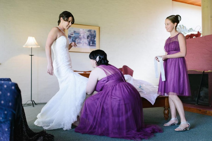 bridesmaid-helping-bride-getting-dressed
