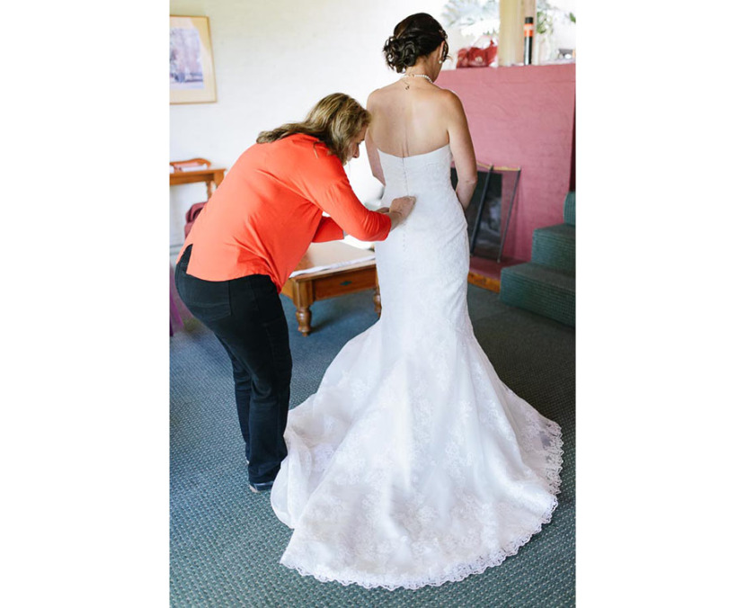 woman-helping-bride-into-wedding-dress