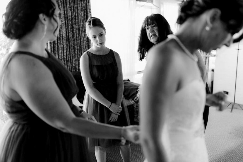 bridesmaids-helping-bride-getting-dressed