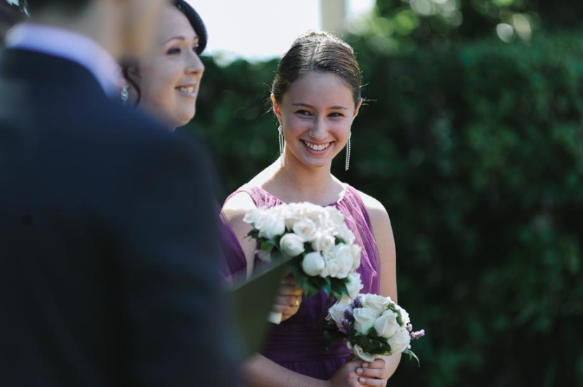 bridesmaid-laughing-during-wedding-ceremony