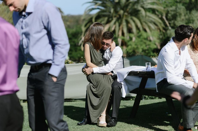 wedding-guests-embracing-on-bench