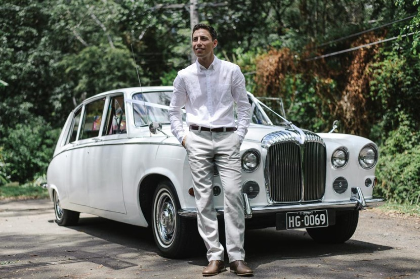 groom-standing-at-wedding-car