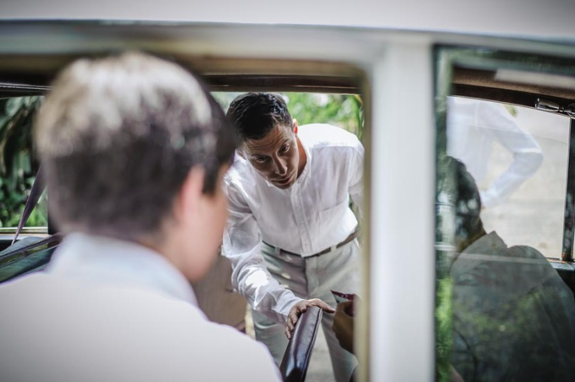 groom-looking-inside-wedding-car