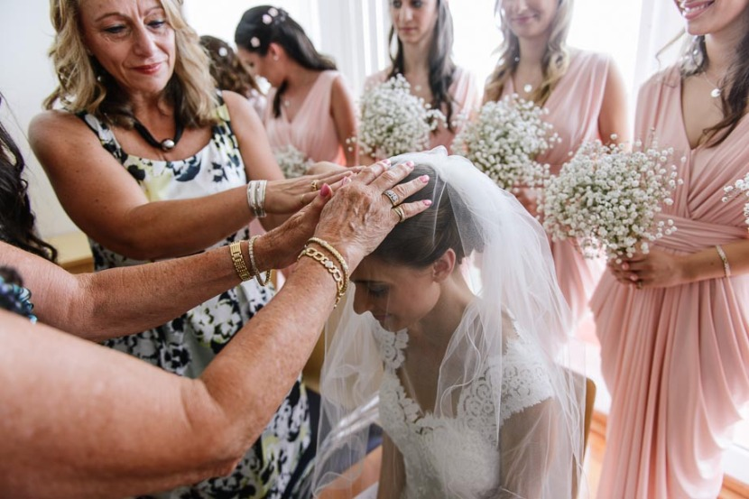 woman-laying-hands-on-brides-head