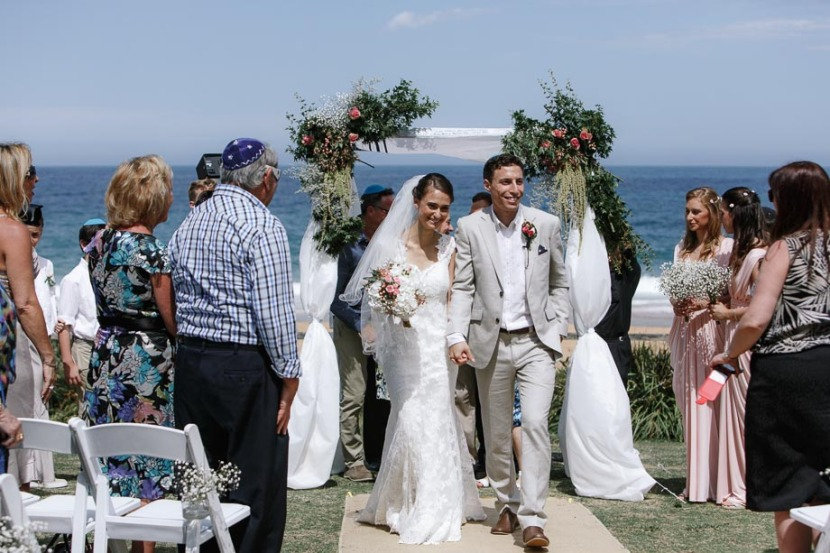 bride-groom-walking-down-beach-aisle