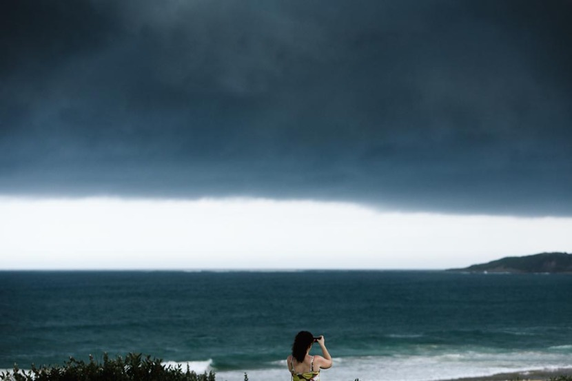 woman-taking-photo-storm-clouds