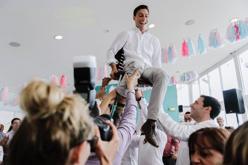groom-on-chair-during-wedding-hora