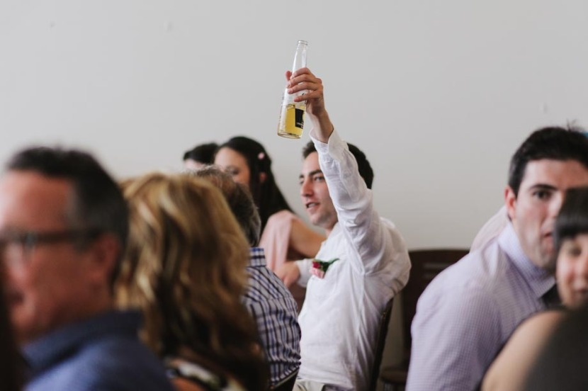 wedding-guest-raising-beer-bottle-toast
