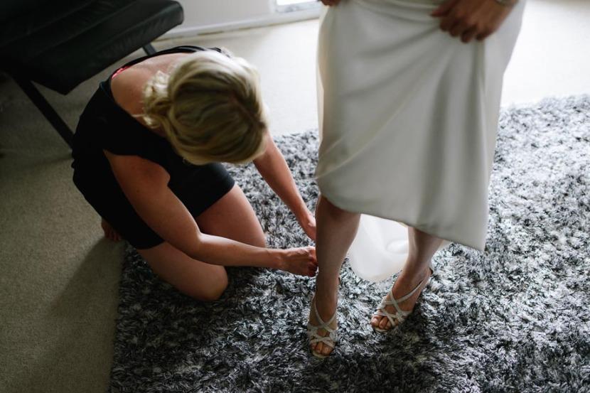 bridesmaid-fixing-brides-wedding-shoes
