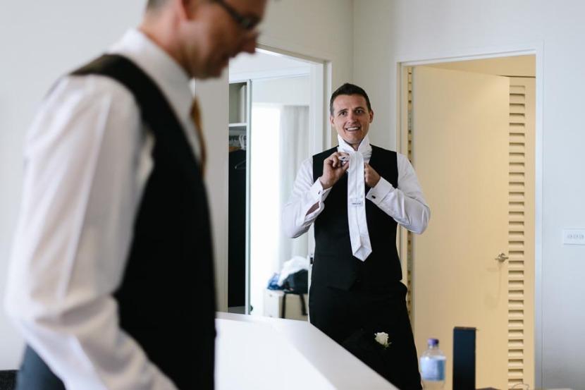 groom-laughing-tying-wedding-tie