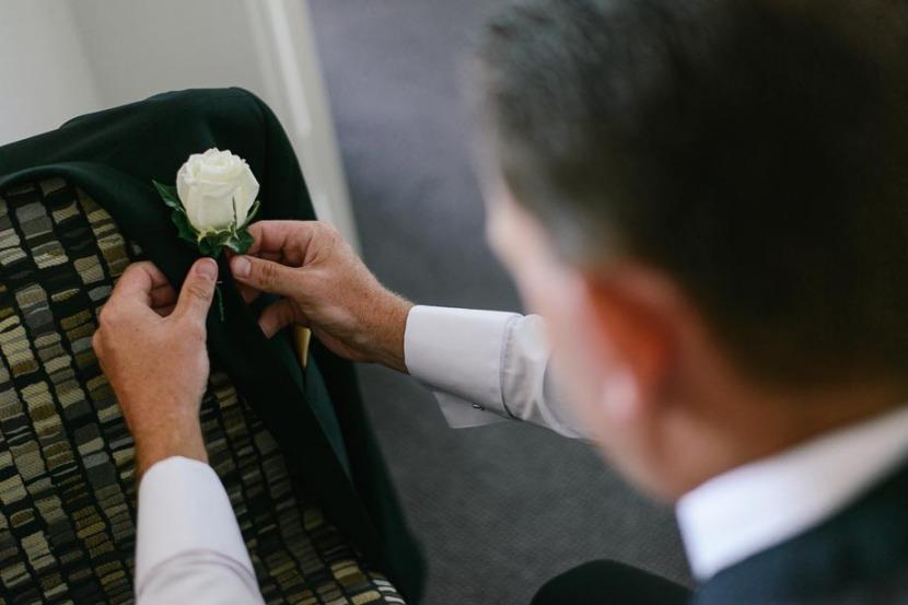 groomsman-applying-wedding-flower