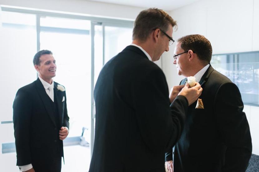 groomsmen-applying-wedding-flowers