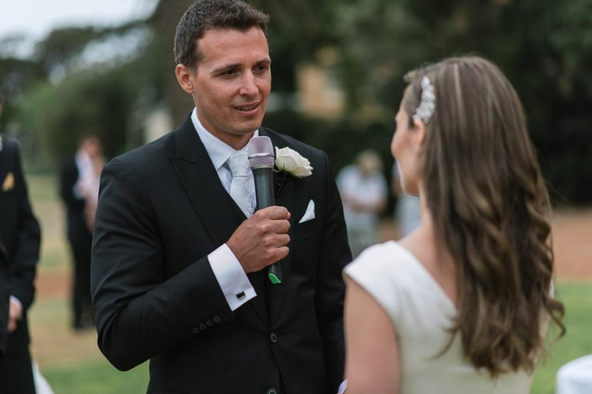 groom-saying-wedding-vows-into-microphone