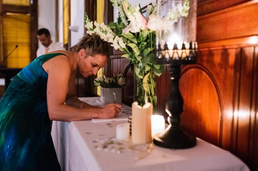 woman-signing-wedding-guestbook