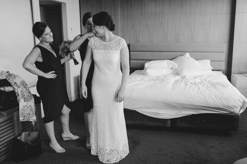 bridesmaids-helping-bride-get-dressed