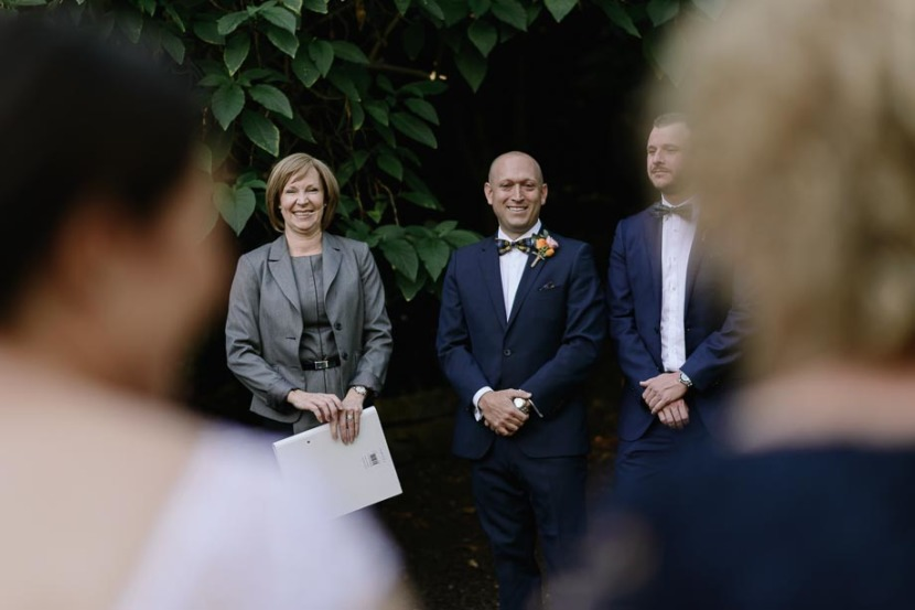 groom-smiling-as-bride-arrives-at-wedding