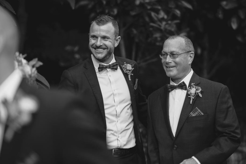 2-men-smiling-during-wedding-ceremony