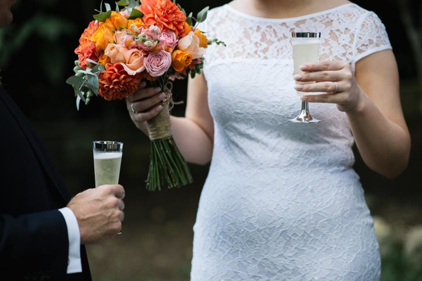 bride-holding-champagne-glass-and-flowers