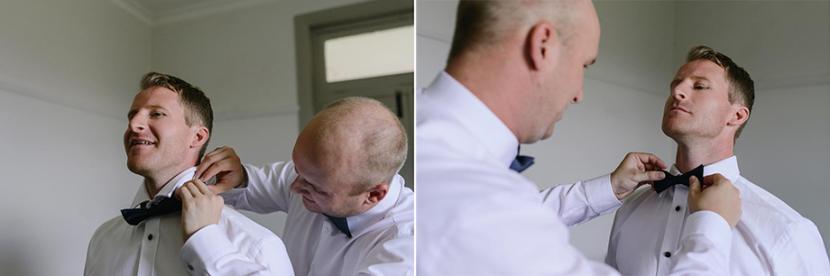 groomsman-tying-grooms-bow-tie