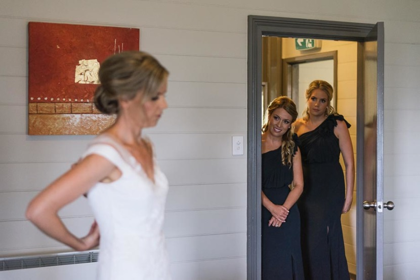 bridesmaids-in-doorway-looking-at-bride