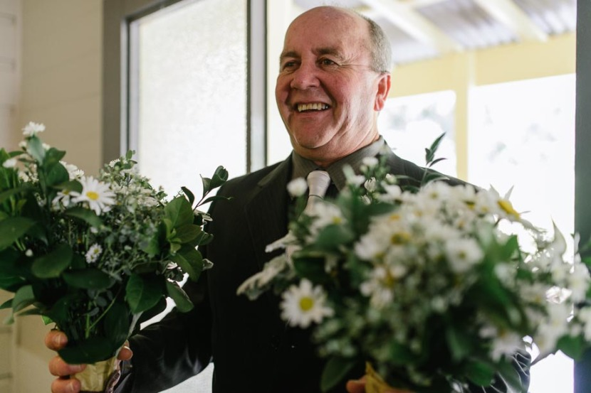 brides-father-laughing-holding-flowers