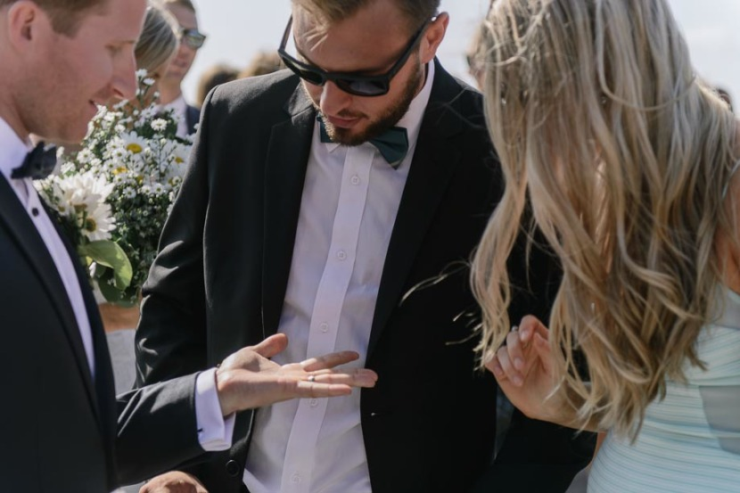 man-looking-at-grooms-wedding-ring