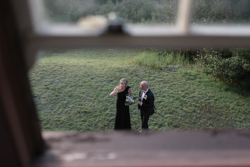 bridesmaid-and-groomsman-outside-window