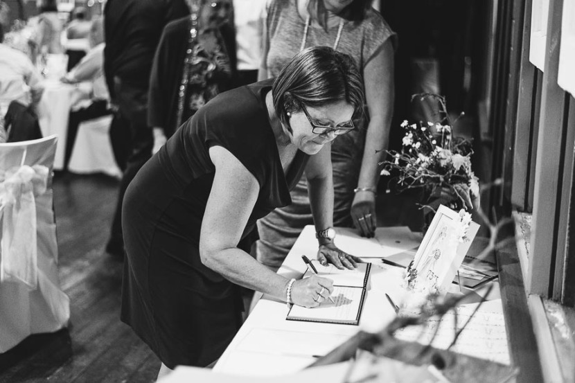 woman-signing-wedding-guest-book
