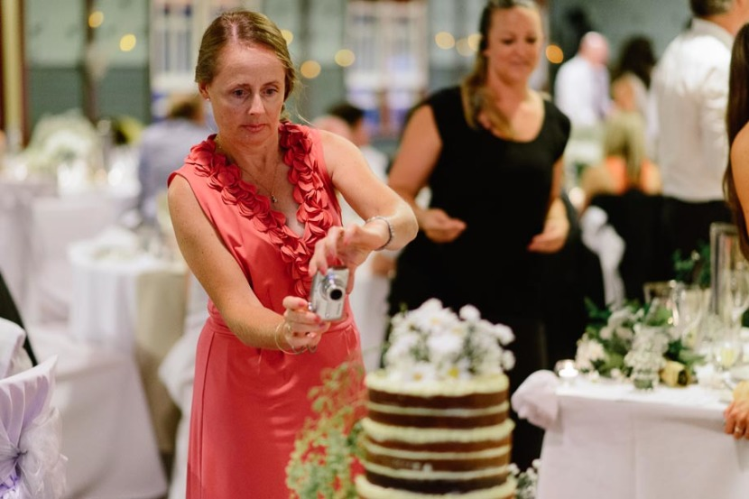 woman-taking-photo-of-wedding-guest
