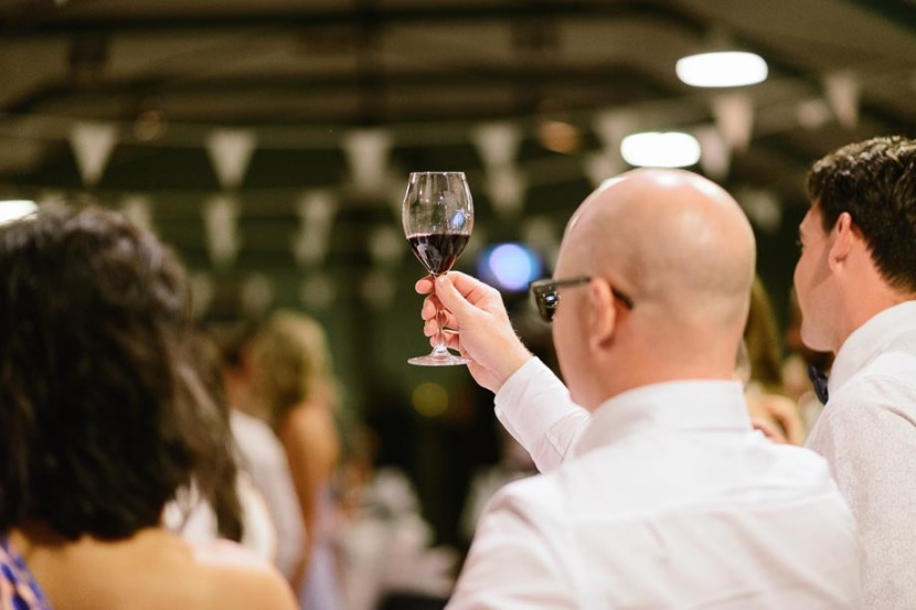 man-raising-wine-glass-during-toast