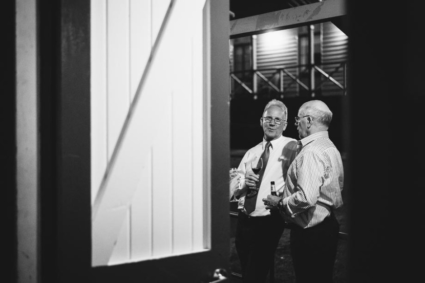 two-men-talking-outside-q-station-wedding