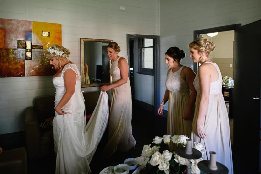 bridesmaids-helping-bride-dress