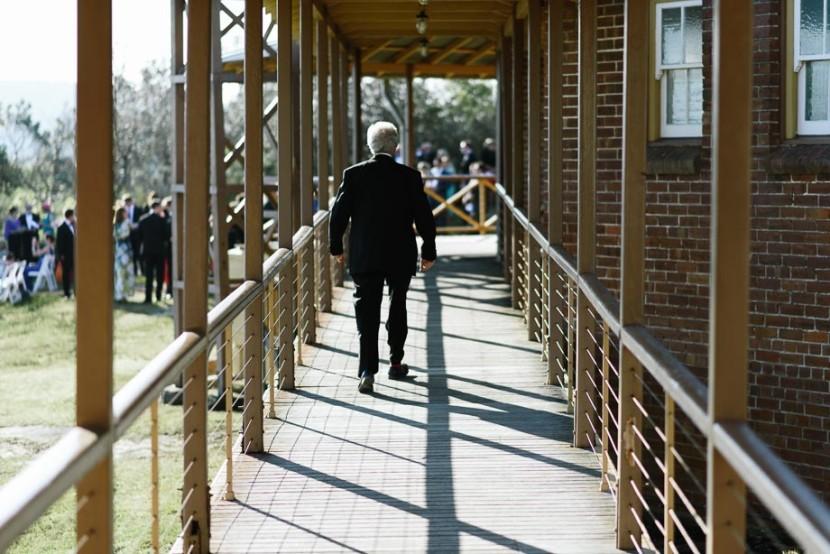 man-walking-along-wooden-balcony