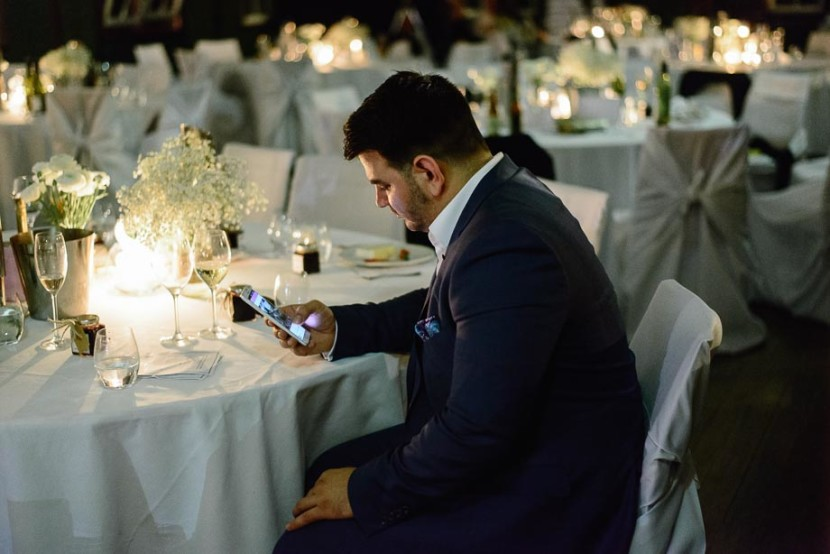 man-sat-on-mobile-phone-at-wedding-reception