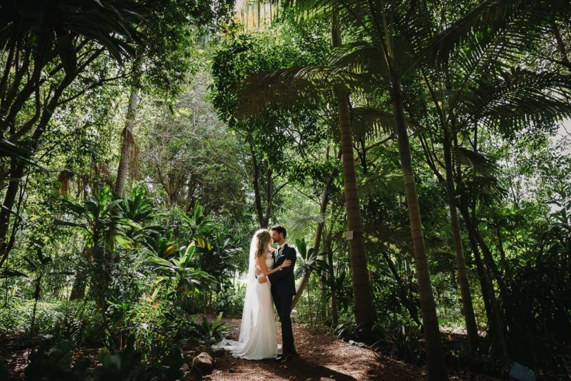 bride-groom-standing-in-botanical-garden-trees