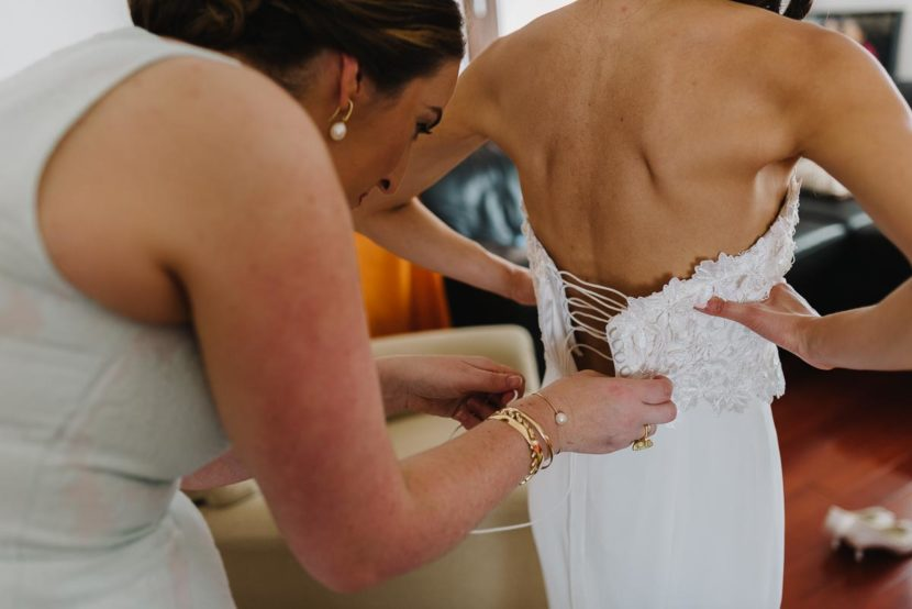 wedding-dress-being-tied-manly-wedding